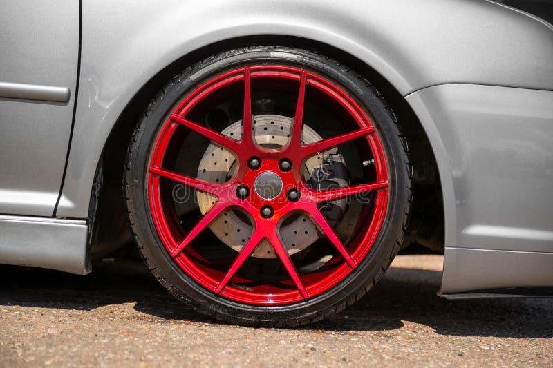 红色糖果在银色斜背式的汽车的色的轻合金轮子 免版税图库摄影