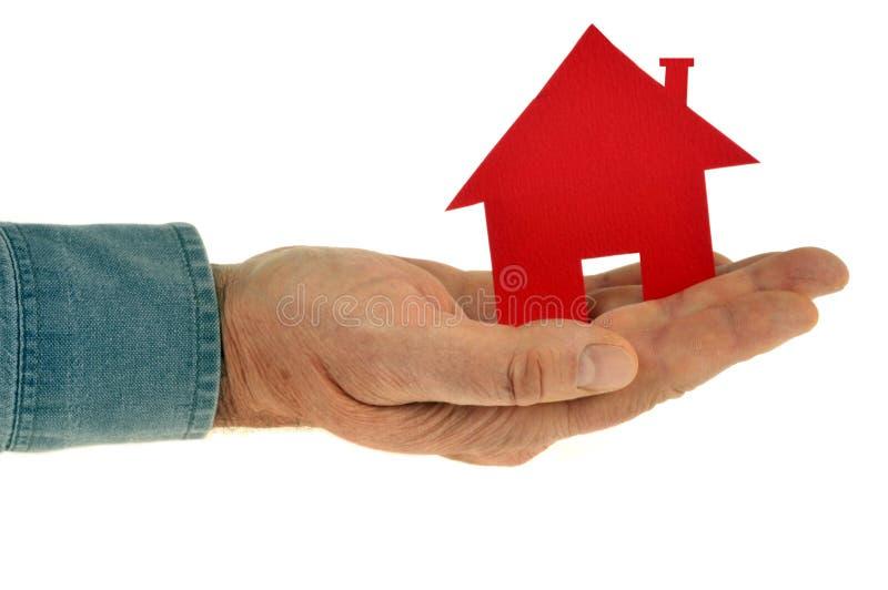 红色纸房子在白色背景的一只手上 免版税库存图片