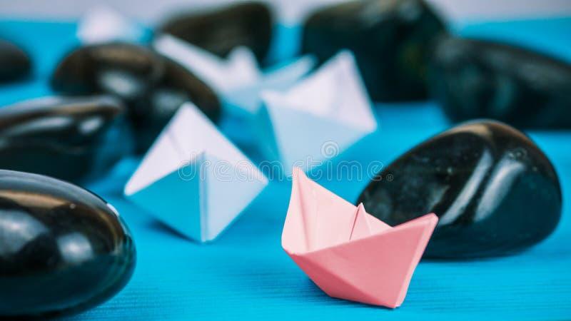 红色纸船领导在抽象岩石石头之间的在蓝色背景 图库摄影