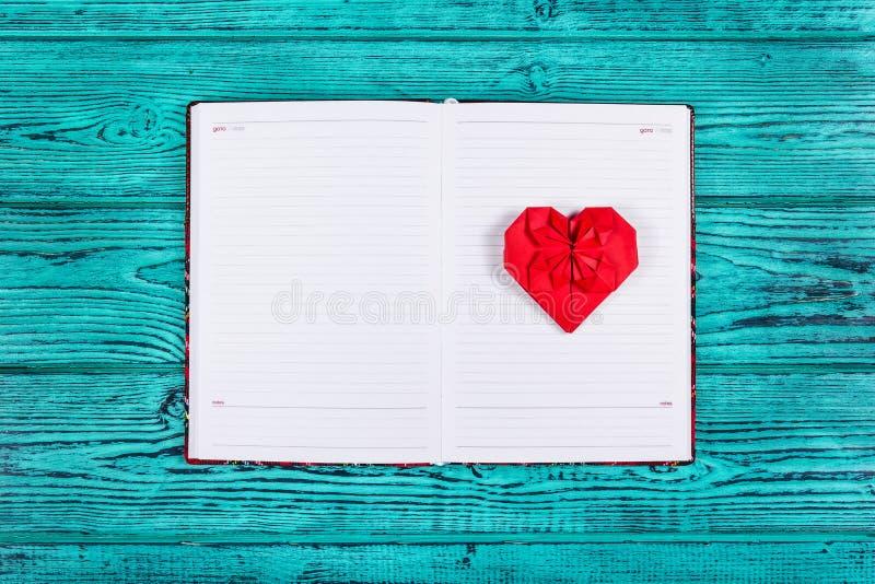 红色纸origami的心脏  打开有干净的页和纸心脏的笔记本 红色心脏和日志在蓝色背景 免版税库存图片