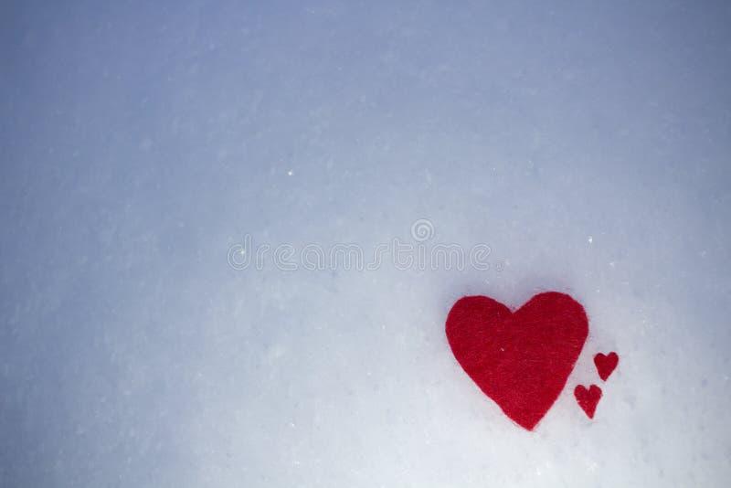 红色纺织品心脏在蓬松冷的雪说谎 免版税库存图片