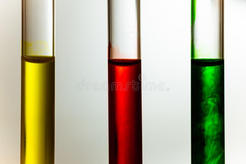 红色绿色黄色解答稀释在试管的清楚的液体 免版税库存图片