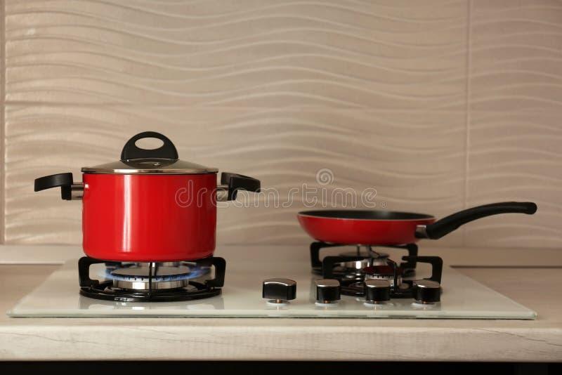 红色罐和煎锅在现代煤气炉 免版税库存图片