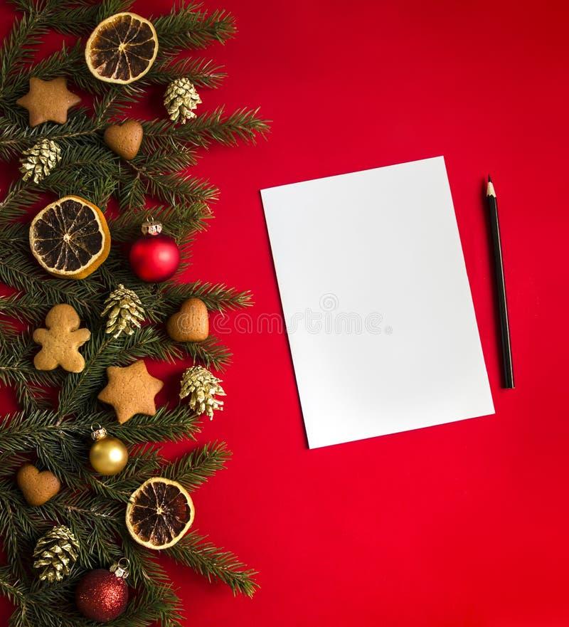 红色背景云杉分支装饰用圣诞节姜饼、金黄锥体、桔子和球和是板料和铅笔 免版税库存照片