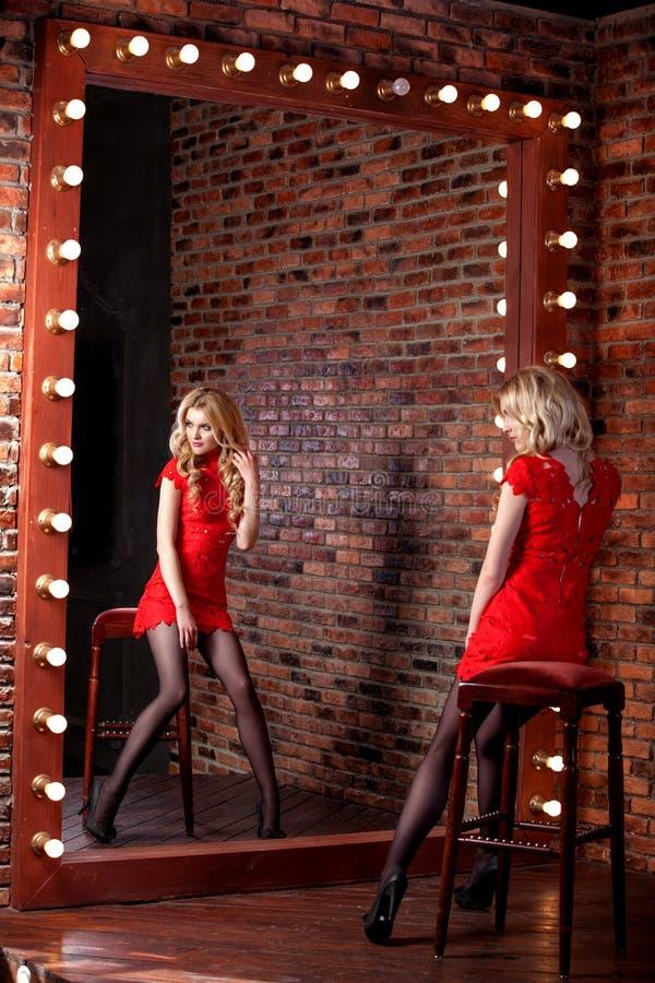 红色背景的美丽的式样女孩 妇女的秀丽 库存照片