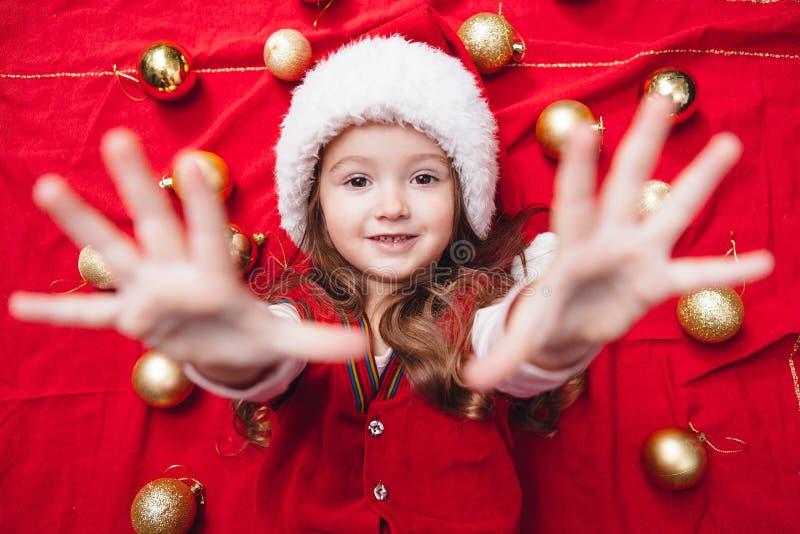 红色背景的逗人喜爱的小女孩提出了她的手 图库摄影
