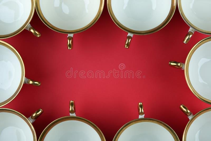 红色背景顶视图上镀金的复古茶杯框 免版税库存照片