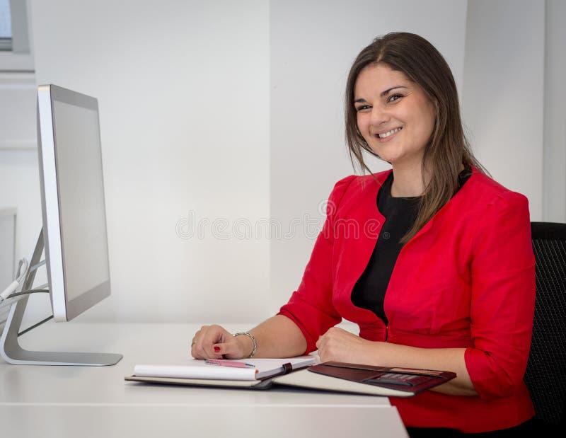红色腰部外套文字笔记的女商人 免版税库存图片