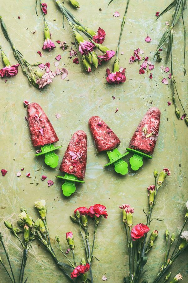 红色自创果子和莓果冰淇凌或者冰棍儿在小野鸭土气选材台背景,装饰用庭院开花,顶面v 库存图片