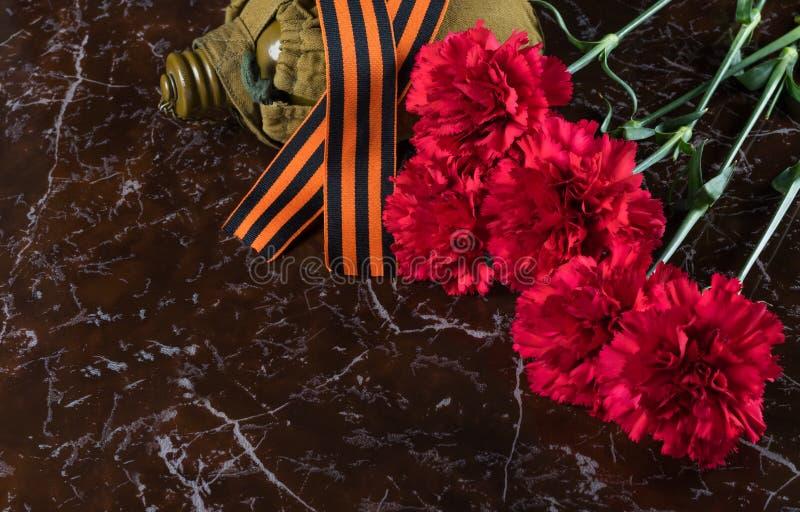 红色花和圣乔治` s丝带在一块大理石平板说谎 免版税库存图片