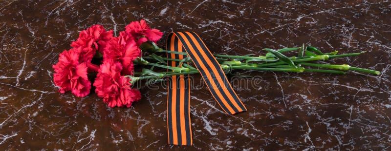 红色花和橙色丝带在一块大理石平板说谎 库存照片