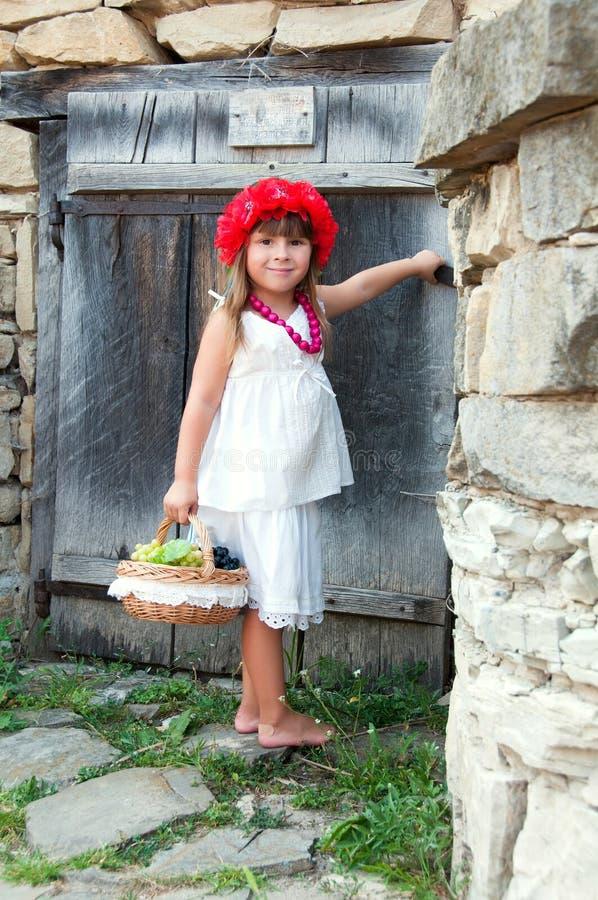 红色花圈的女孩在石建筑附近开花与苹果篮子的鸦片  图库摄影