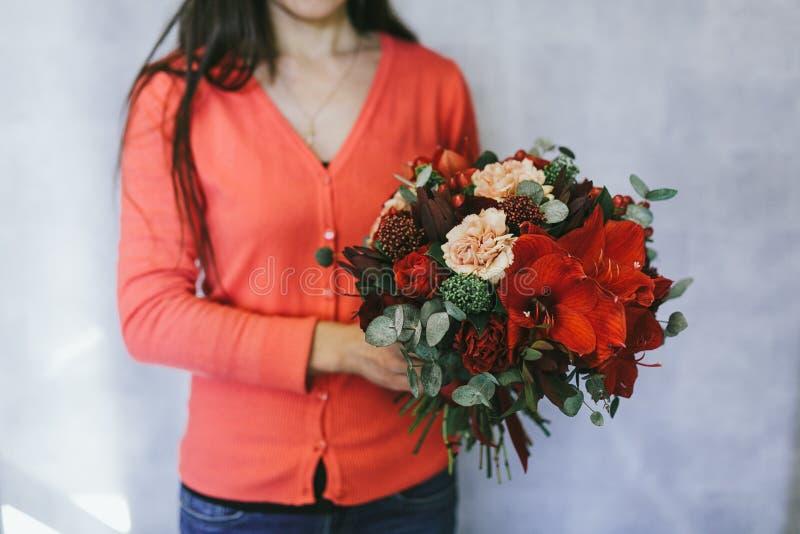 红色花花束在妇女的手上 免版税库存照片
