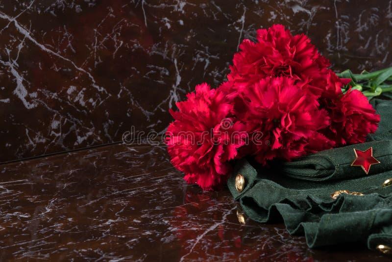 红色花,军服在一块大理石平板说谎,在左边是题字的一个地方 免版税图库摄影