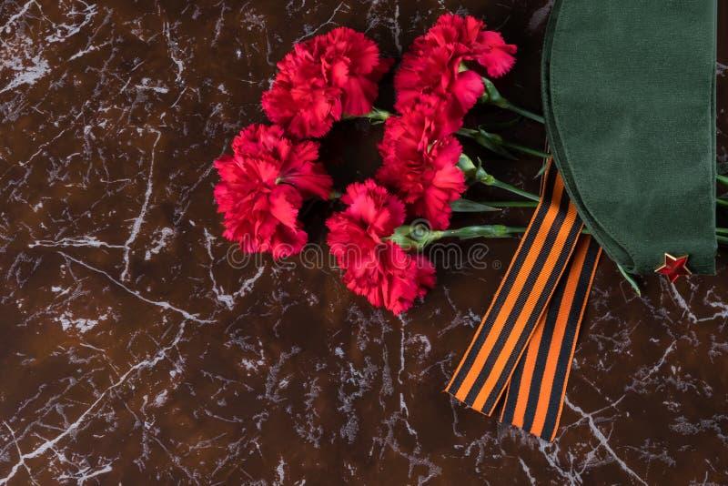 红色花,有一句红色星谎言的军用盖帽在一块大理石平板 库存图片
