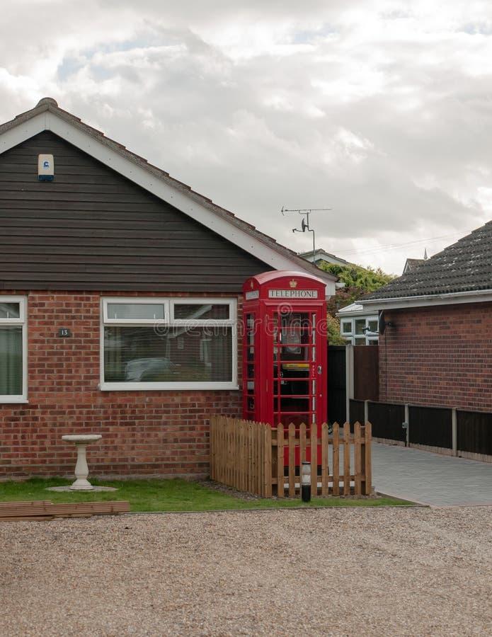 红色英国电话亭在房子外面 库存照片