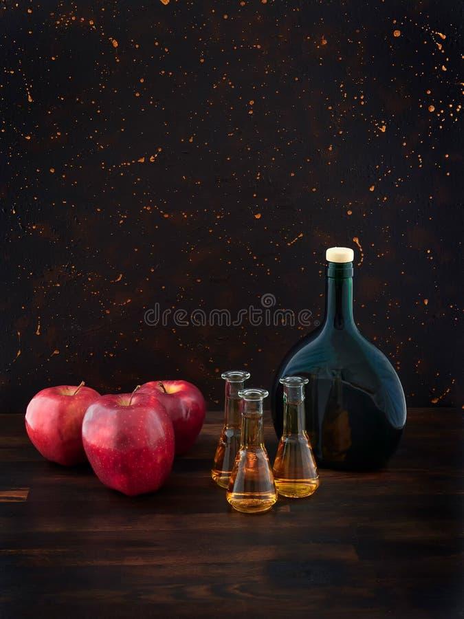 红色苹果、杯苹果白兰地酒或卡尔瓦多斯和一个绿色瓶 图库摄影