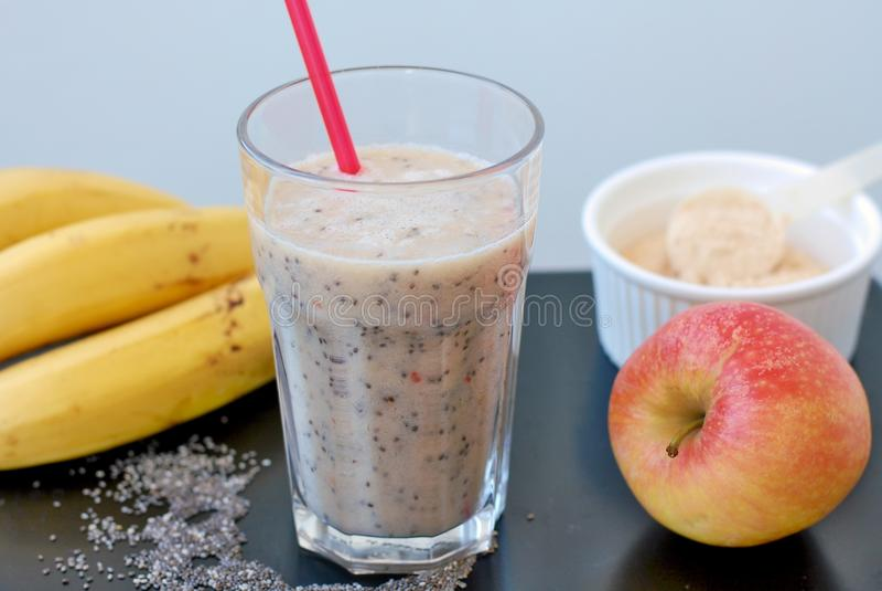 从红色苹果、香蕉chia种子和植物蛋白粉末的健康新圆滑的人饮料在与秸杆的玻璃 免版税库存图片