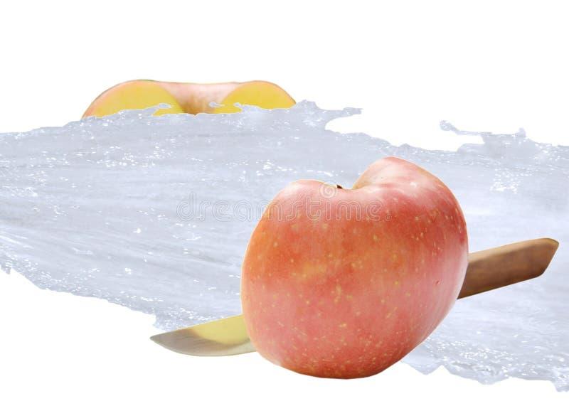 红色苹果一半由飞溅在白色背景的刀子和水切开了 免版税库存图片