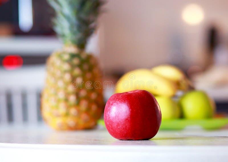 红色苹果和异乎寻常的果子在桌上 库存图片