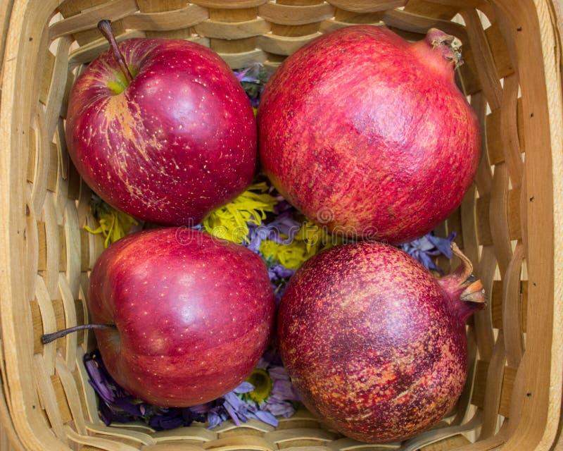 红色苹果和石榴在柳条筐放置 免版税图库摄影