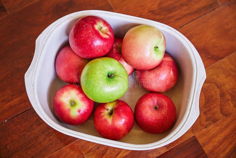 红色苹果和绿色苹果在白色塑料碗在棕色木地板上 免版税图库摄影