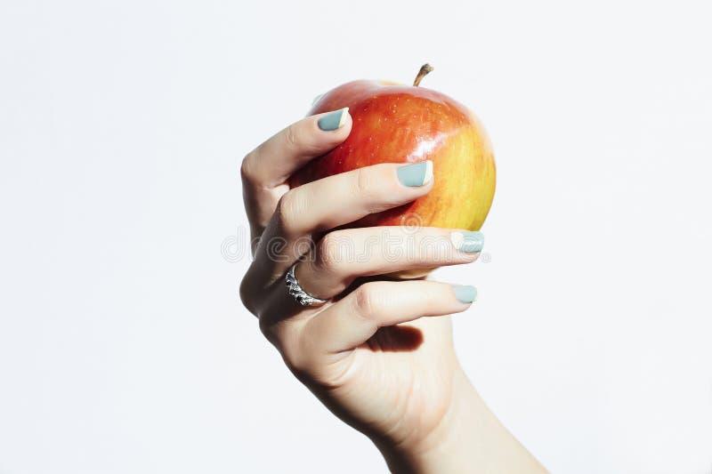 红色苹果在手中与修指甲 女性现有量 美容院妇女紫胶擦亮剂 免版税图库摄影
