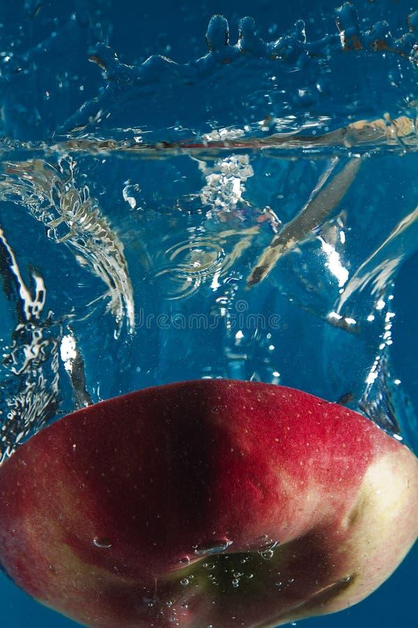 红色苹果在水中切成了两半 免版税库存照片
