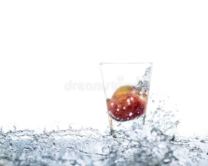 红色苹果有droping对玻璃和飞溅水在Th附近 免版税库存图片