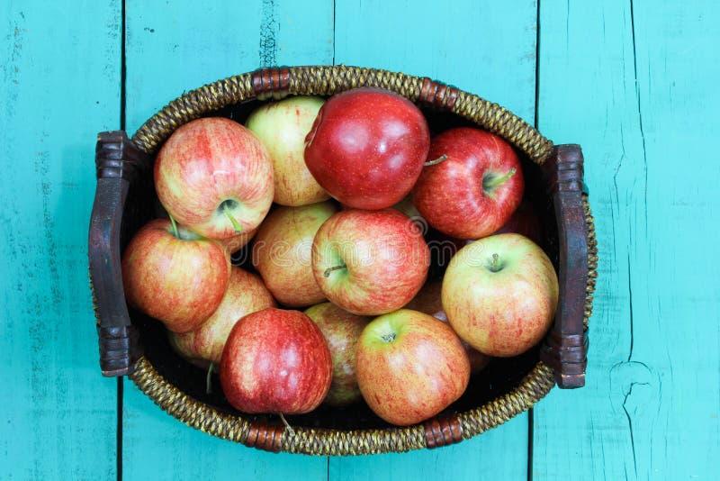 红色苹果篮子坐木桌 图库摄影