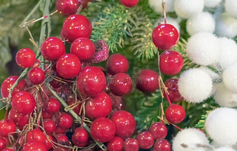 红色莓果和白色蓬松球在圣诞树的背景 免版税库存照片