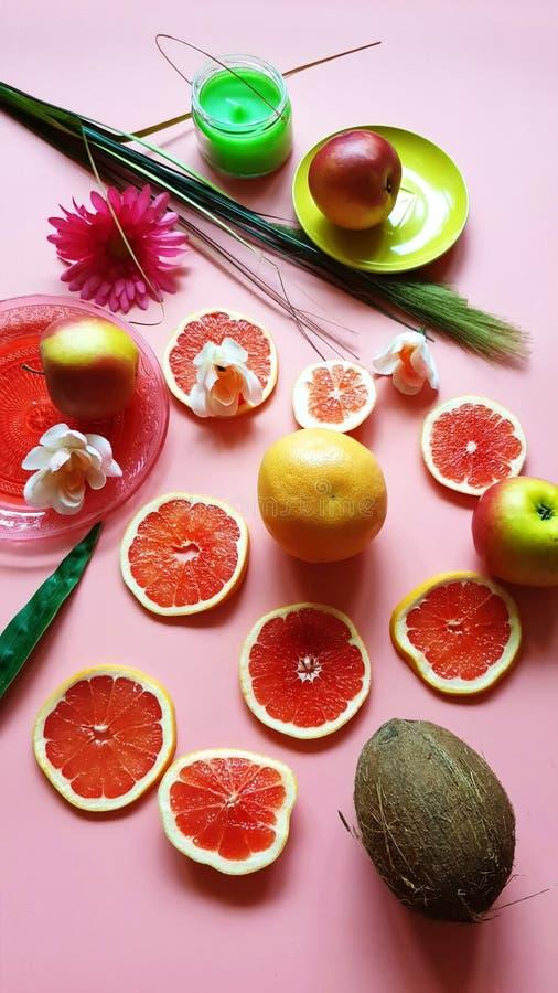 红色葡萄柚切黄色柑桔水多的黏浆状物质青绿的红色黄色桃红色盘杯子和板材健康食品设计stil 免版税图库摄影