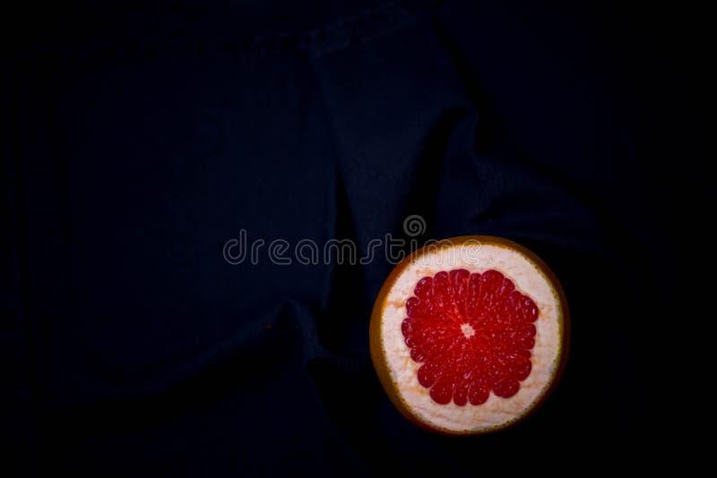 红色葡萄柚美好的明亮的水多的片断在黑背景的在黑黑暗的背景的中间底部与 免版税库存照片