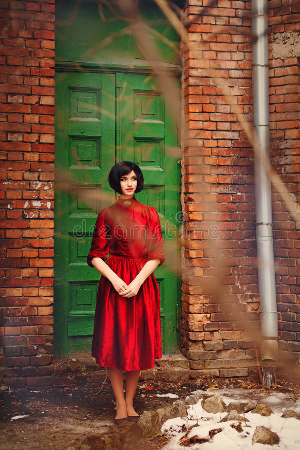 红色葡萄酒礼服的女孩浅黑肤色的男人是常设近的老门 库存照片