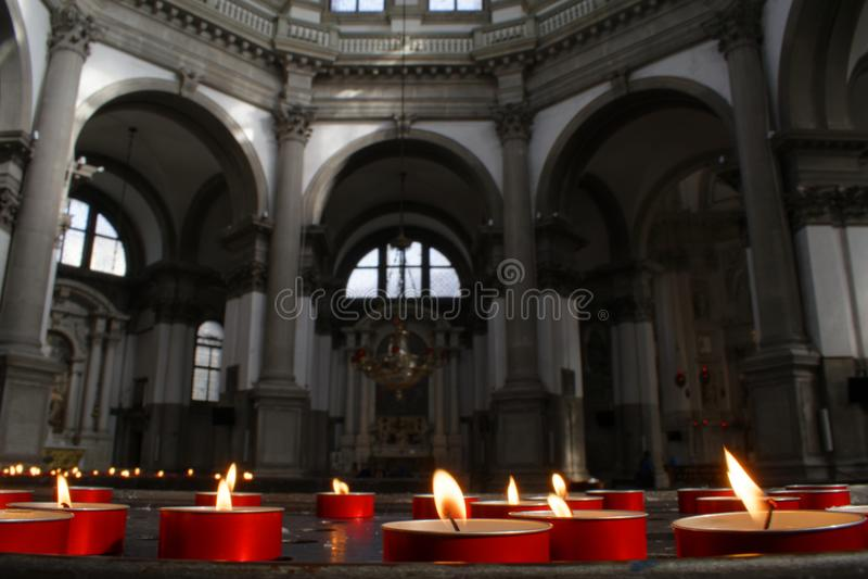 红色蜡烛和教会内部,威尼斯,意大利 免版税库存图片