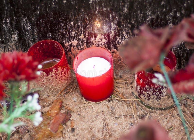 红色蜡烛站立在公墓的边路的-记忆的标志 库存图片