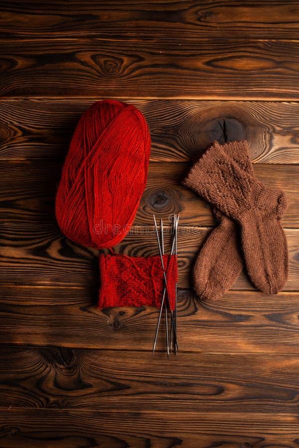 红色螺纹、编织针和棕色袜子球在木背景 库存照片