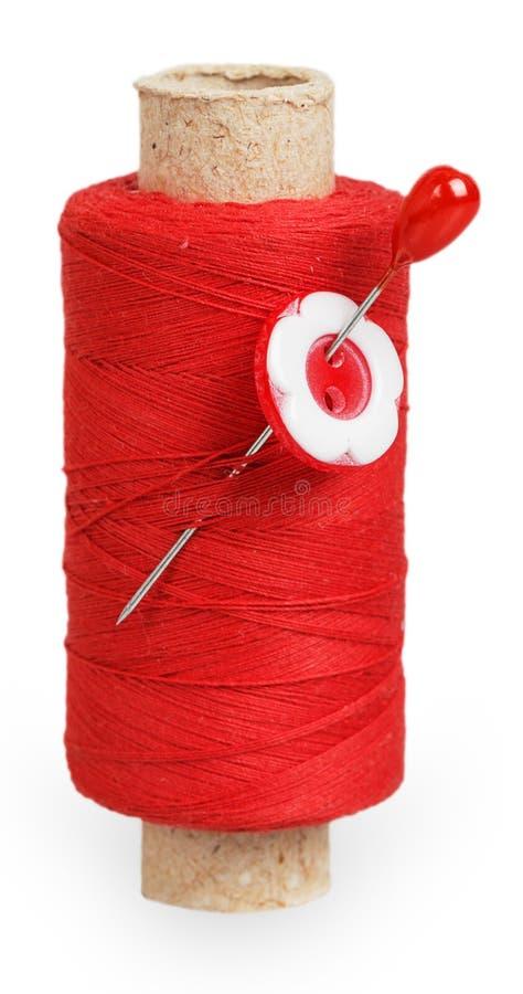 红色螺纹卷与红色按钮的在别针 免版税库存照片