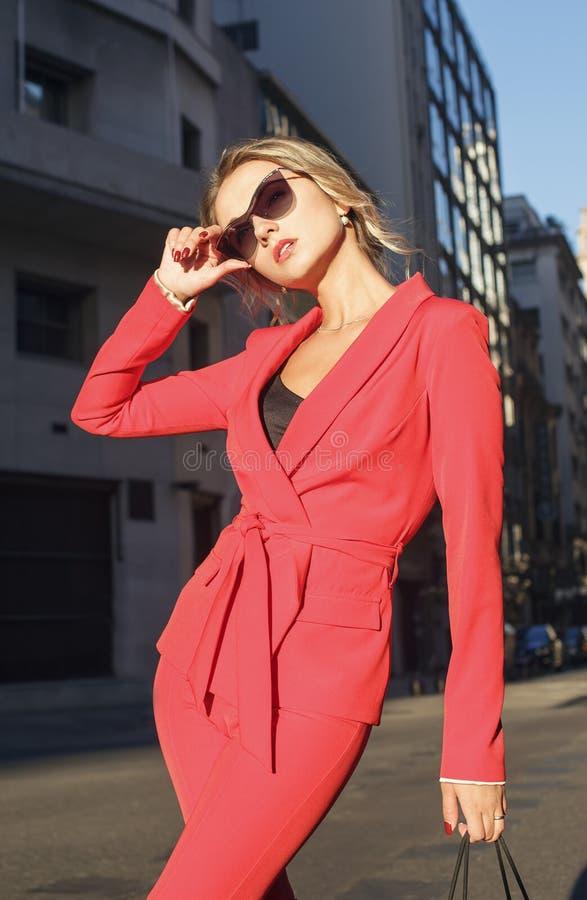 红色衣服和太阳镜的时兴的白肤金发的妇女 库存照片