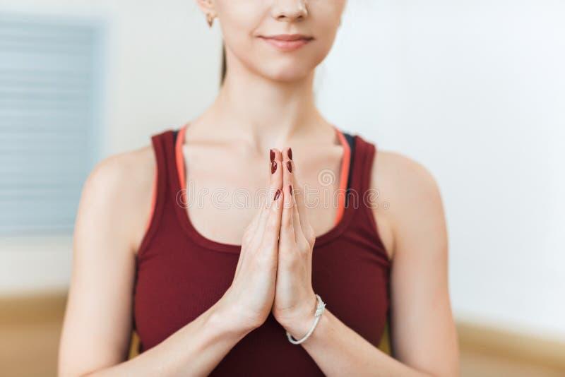 红色衣服实践的凝思的少妇在瑜伽类的健身房 放松和舒展 手的克洛德在Namaste pos 免版税库存照片