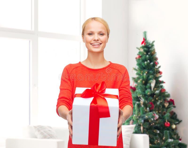 红色衣裳的微笑的妇女有礼物盒的 库存图片