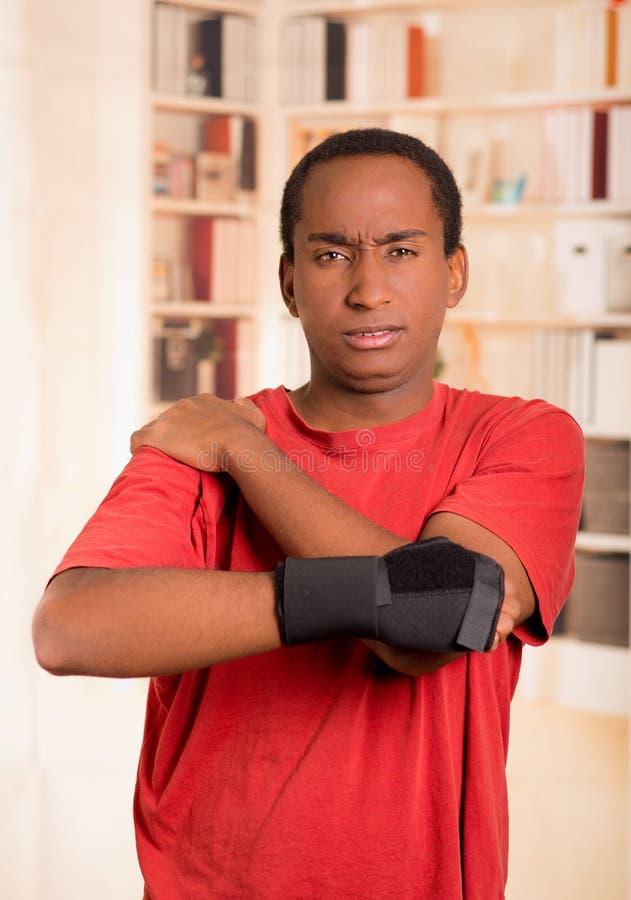 红色衬衣佩带的腕子括号支持的人在摆在为照相机的右手,拿着他的与其他胳膊的肩膀 库存图片