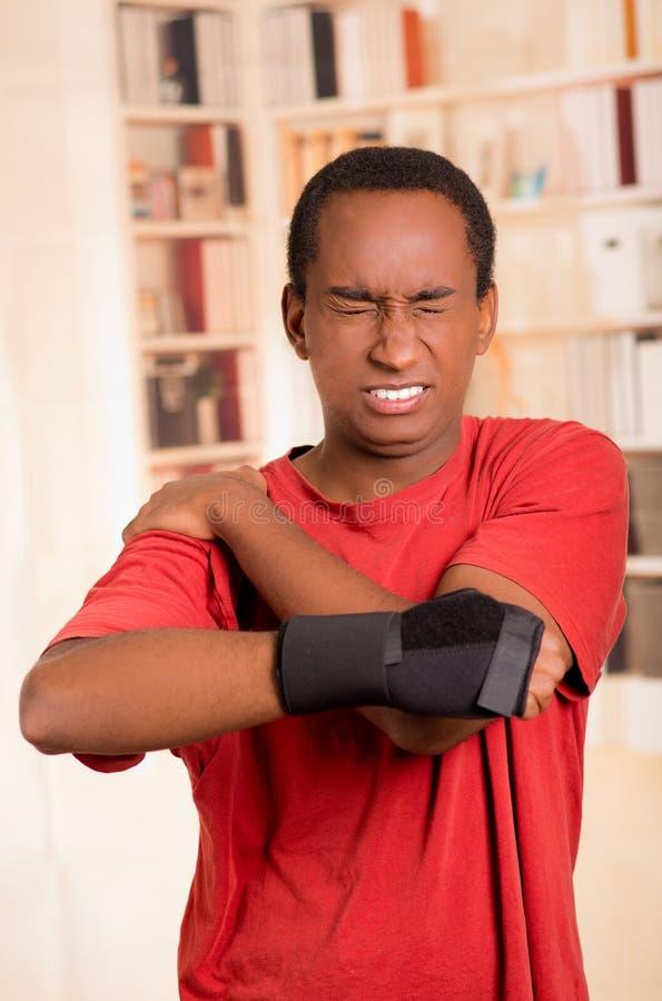 红色衬衣佩带的腕子括号支持的人在摆在为照相机的右手,拿着他的与其他胳膊的肩膀 免版税库存图片