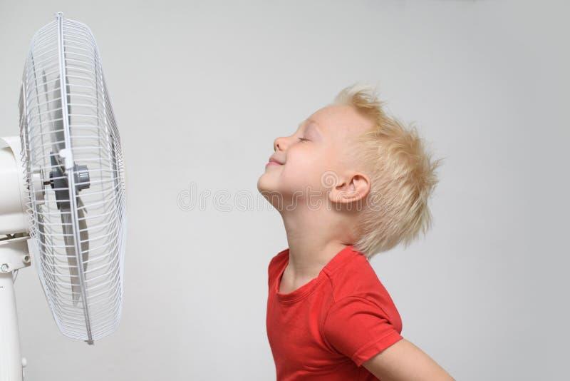 红色衬衣和闭合的眼睛的俏丽的微笑的白肤金发的男孩享用凉快的空气的 E 免版税库存照片