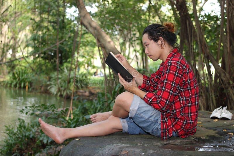 红色衬衣的在美好的自然背景中的年轻轻松的人画象读一本书 免版税库存照片
