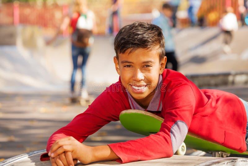 红色衬衣的愉快的阿拉伯男孩在滑板放置 图库摄影