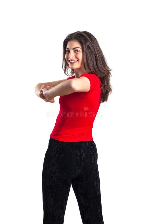 红色衬衣的美丽的深色的少年体育女孩是exercisin 免版税图库摄影