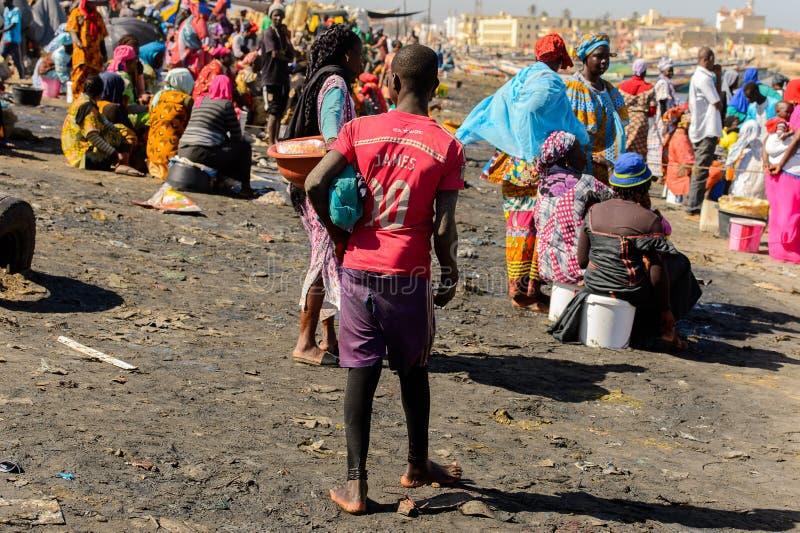 红色衬衣立场的不明身份的塞内加尔男孩从后面  库存图片