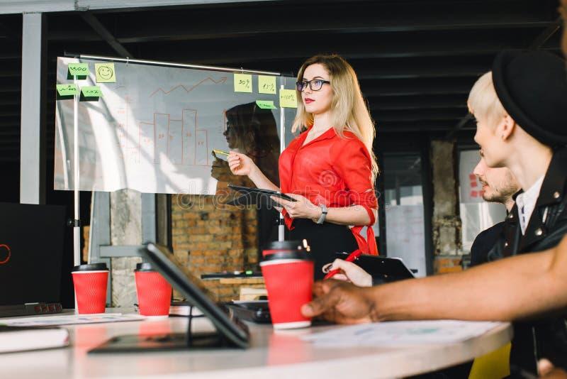 红色衬衣评论的销售的结果的确信的女实业家对见面的同事 自由职业者,团队工作 库存照片