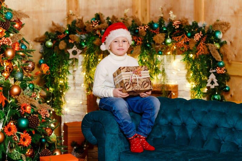 红色袜子和牛仔裤的七岁的孩子坐长沙发在与一件礼物的圣诞树附近在他的手上 免版税库存图片